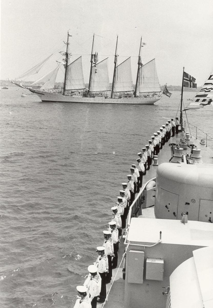 """Enkeltbilde. Fregatten KNM Trondheim, besøker New York under 200-års jubileum 4/7-1976. Oppstilt for manning av relling. I bakgrunnen den spanske toppseilskonnert """"JUAN SEBASTIAN DE ELCANO"""" som deltok i Operation Sail"""