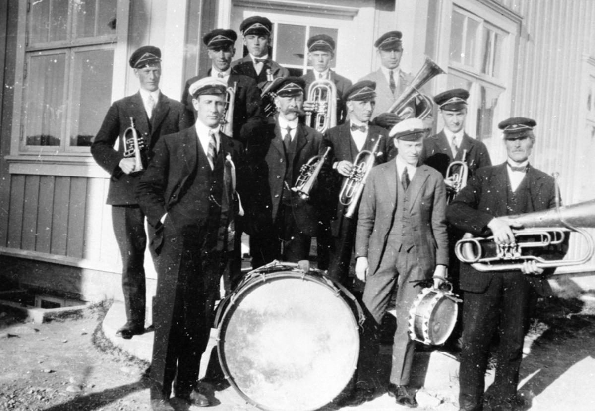Brumunddal Musikkforening. Foran venstre er Johannes Sørlien, Fredrik Græsby, Sigurd Evensen, Nils Johansen Hegre. I midten er Hans Bakken, Johan Røhne. Bak er Haakon Græsby, Hans Stordahl, Per Hangenholen, Hans Berger, Martinus Larsen, 17. mai, posthustrappa, Brumunddal.