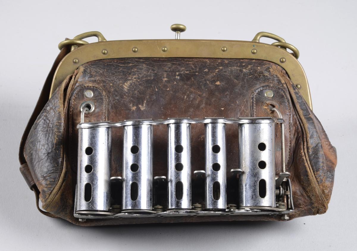 Skinnveske for billettsalg ved kollektiv transport.  Vesken har midtstilt lås i metall, som låses når man klemmer den igjen. Åpnes ved å løfte på låseknappen. På fronten av vesken er det to rektangulære vertikale lommer som er forsterket, her settes mynteholderen i. Myntholderen er løs, laget av metall, og har fem rom for mynter med hver sin bryter. Når bryteren klemmes ned blir en mynt ført ut av holderen. Vesken har en reim som går under vesken og ender opp på motsatt side på baksiden av vesken. Disse kan festes i en skulderreim. Fòr i bomullslerret, to åpne lommer i siden.