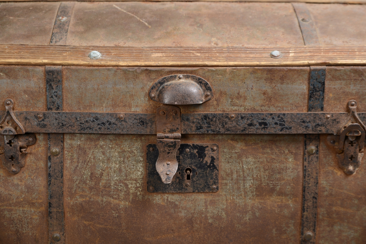 Rektangulær kiste av tre og blikk med avrundet lokk. Kista er hengslet og har tre låser. Den er forsterket med trelister og metallbånd. Innvendig er kista trukket med blåstripete papirtapet. Den er delvis inndelt i rom ved hjelp av bomullsbånd. Lokket har et håndtak i metall på langsiden. Kista har også håndtak på hver kortside.