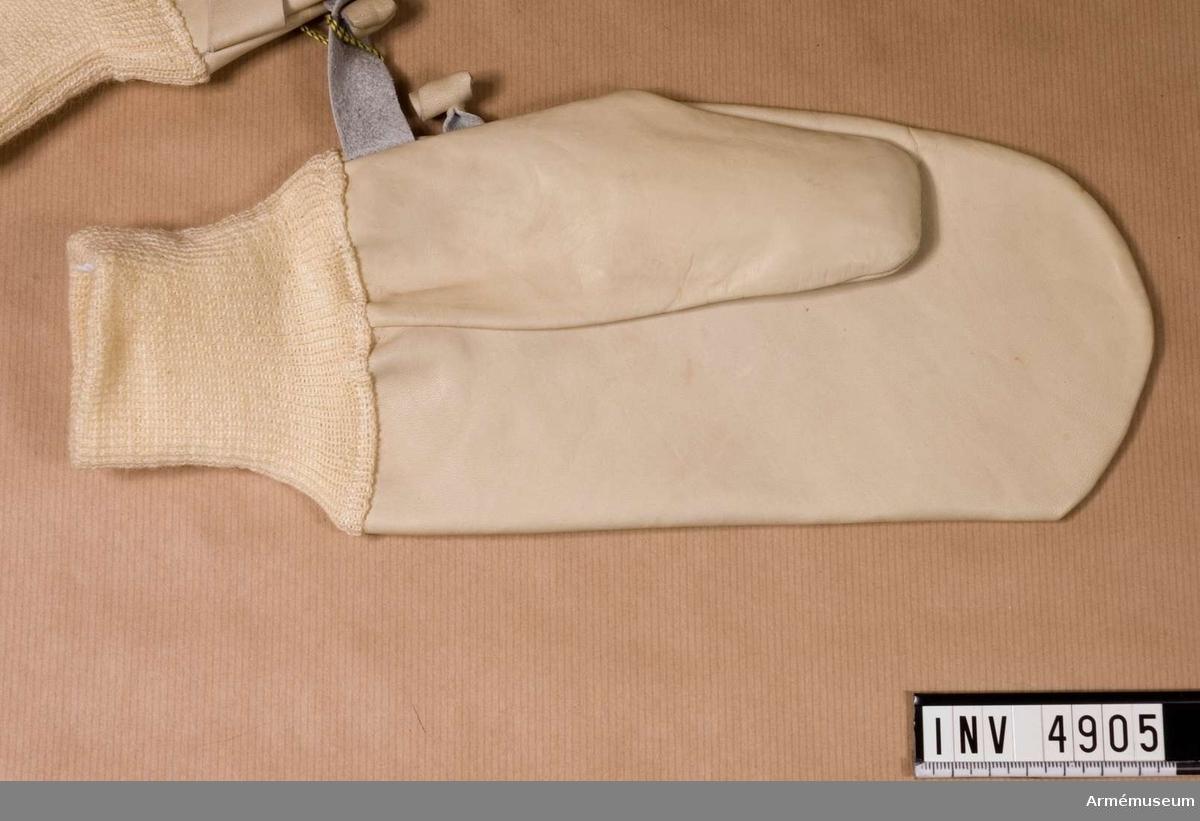 Handske, tum-, Svea livgarde. Med stickad, vit mudd. På tumsidan hank/knapp för hopfästande av handskarna. (M 7331-212000).