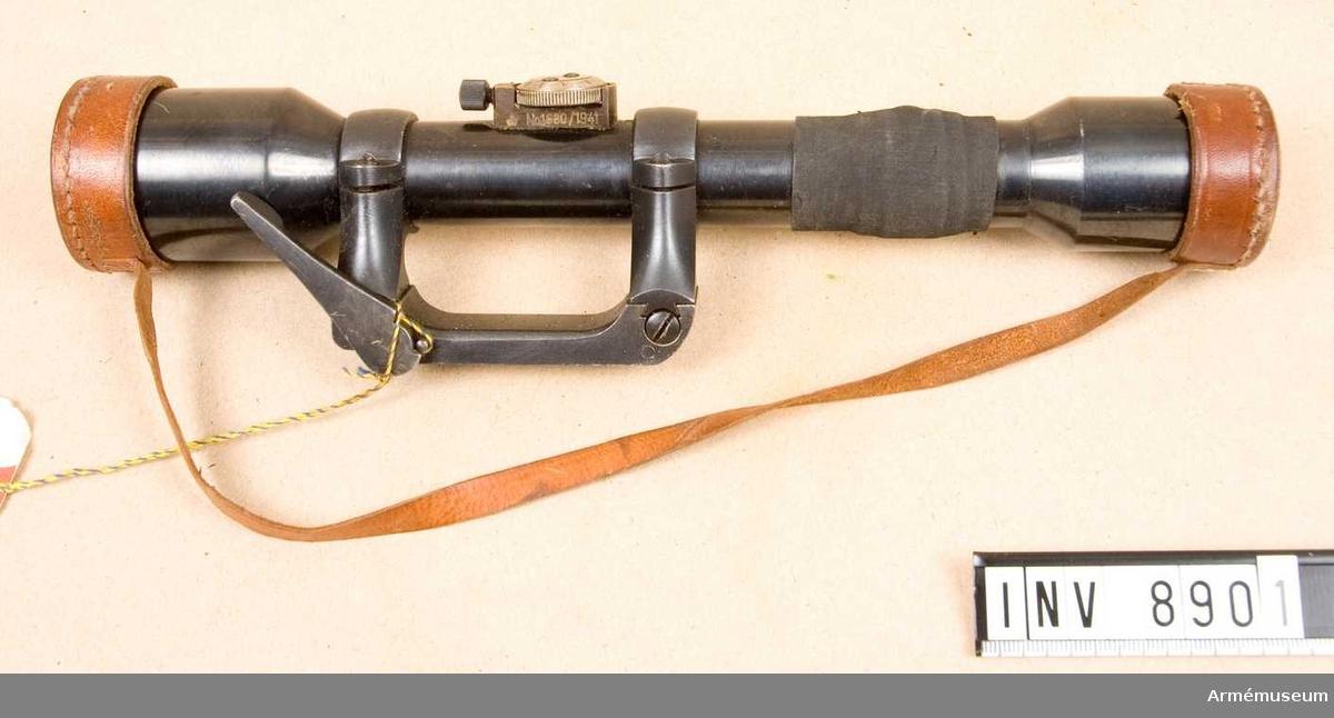Samhörande nummer är 8901-8902.Kikarsikte m/9141, Ajack, till gevär m/1896 system Mauser.Tillverkningsnummer 1680/1941. Märkt: Ajack 4 x 90. Hållare för kikarsikte försök, tillverkare Kungl  Armétygförvaltningen, tillverkningsnummer 4923.Bestående av:  1 st kikarsikte med hållare, 1 st linsskydd av läder.Kikarsiktet passar till gevär m/1896 AM 6948.Samhörande: AM 8901 Kikarsikte med hållare, AM 8902 Kikarfodral av järnplåt.
