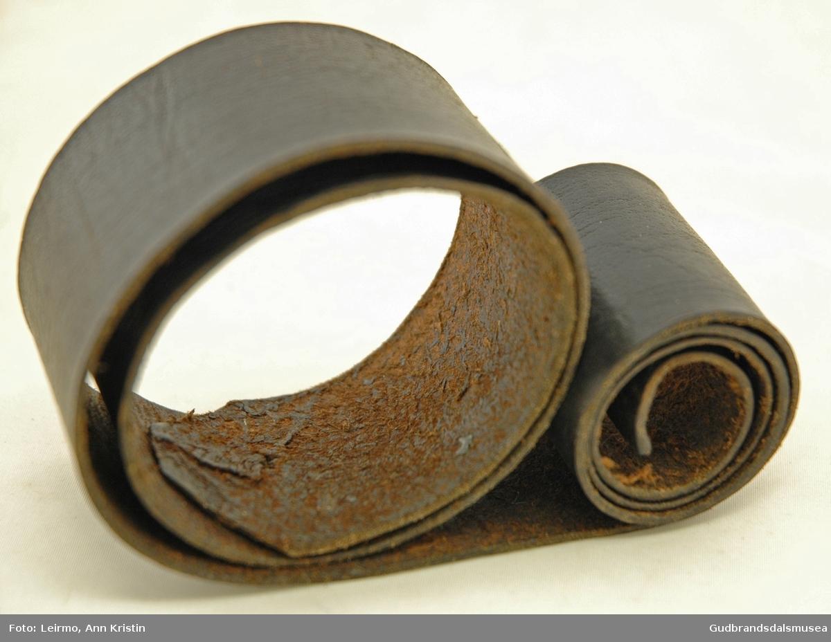 Lærreim brukt til sliping av barberkniv, er flat og tynn, har tillaget hull på ene enden.