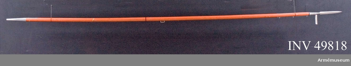 Grupp D I. Spjutbladet är tveeggat med höga ryggar. Den koniska holken har ringformigt förstärkt kant. Skaftskenorna utgå från spetsens eggsidor och hålls fast av tre genomgående skruvar, vilkas huvud är utbildade till flata knappar, som skulle fasthålla flaggan. Nedtill på holken finns flera bokstäver och siffror inslagna. Skaftet är rödmålat. Tyngdpunkten är utmärkt med en rand. Litet framför denna rand är en rektangulär järnögla islagna i skaftet.Doppskon är konisk och har rätt kortare skenor. Vid skaftets ögla är rester av en rundflätad armrem fastgjorda.Dylika lansar var i bruk 1816-82.  Mått: Spjutbladets längd 21,5 cm Spjutbladets största bredd 2,6 cm Skaftskenornas längd 31,5 cm Skaftskenornas bredd 1,4 cm Skaftets största tjocklek 3,7 cm Doppskons längd 18,5 cm Doppskenornas längd 11 cm Doppskenornas bredd 1,5 cm