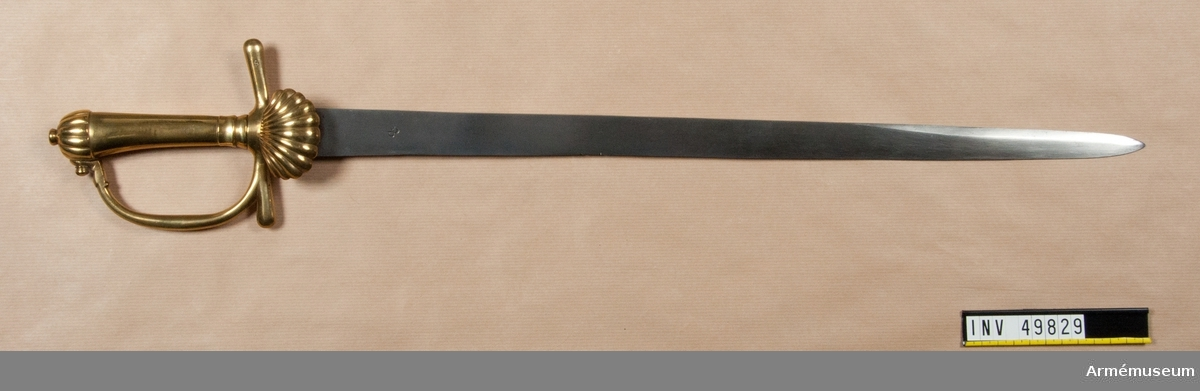 Grupp D II. Parerstångens längd 120 mm. Klingans bredd upptill 31 mm.  Klingan synes vara en bajonettklinga från 1700-talets början eller förra hälft. Den är rak samt till större delen av sin längd eneggad, men 17,5 cm ovanför udden får den egg även på ryggsidan. Upptill på klingans innersida finns en P-stämpel och en bit nedanför fästet sitter på klingans yttersida en stämpel, som ser ut som en med stjälk försedd treklöver.  Fästet är helt av mässing. Knappen är halvklotformig, men har  ovalt tvärsnitt. Den prydes med 10 vertikala räfflor. På  översidan har den nitknapp, som med den närmast cirkelrunda  foten är 0,6 cm hög och som har en diameter på 1,1 cm.  Nitknappen har formen av en omvänd kon. Kaveln är vidare  uppåt och har en slät fram- och bakkant, men yttersidan och  innersidan är slät och avrundad.  Parerstången är rak med  spetsovalt tvärsnitt och blir något vidare mot de avrundade  ändarna. På den bakre armens yttersida är siffran 6 inslagna.Handbygeln har spetsovalt tvärsnitt, är tjockast på mitten och dess övre ände är fäst med en skruv vid knappen. Upptill på innersidan finns en liten stämpel med bokstäverna C G L under en krona. På yttersidan finns vid korset en ganska liten, nedbjöd, kupig parermussla, som på utsidan prydes av 10 strålformig utgående räfflor.