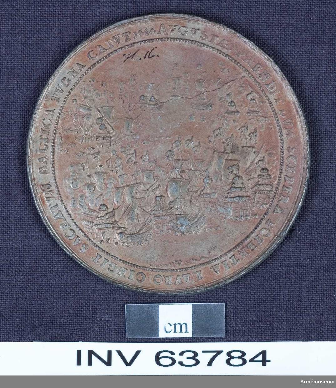 """Grupp M. Medalj av 25. storleken. Kristina fullmyndig såsom drottning den 7 december 1644.  Medaljen är av svagt förkopprat tenn. ÅTSIDAN: """"IMPERIVM PROLES GVSTAVI MAXIMA MAGNI SVSCIPIT INNVMMERIS VIVAT CHRISTINA TRIVMPHIS"""". Drottningen i kunglig mantel och har strålkrona på huvudet och spira i hand. Hon står med en talares åtbörd framför sin tron under en himmel. Till höger, framför sina stolar, står de fem förmyndarna drotsen, marsken, amiralen, kanslern och skatt- mästaren, hållande regalierna. Till vänster står de fyra riks- ståndens representanter. I den lägre förgrunden ses åtskilliga andra personer. Den krönta svenska riksskölden ligger framför drottningen och lutad mot tronens trappsteg. Inom omskriften en ornerad rand. Nederst på en liten fyrkantig platta: """"S.D.""""  FRÅNSIDAN: """"AVGVSTAE PRENDIT DYM SCEPTRA POTENTIA LAVRO CINGIT SACRATVM BALTICA PVGNA CAPVT 1644"""". Svenska och danska flottornas strid vid Femern. Inom skriften en fin bladkrans. På ett av skeppens akterspegel: """"D""""."""