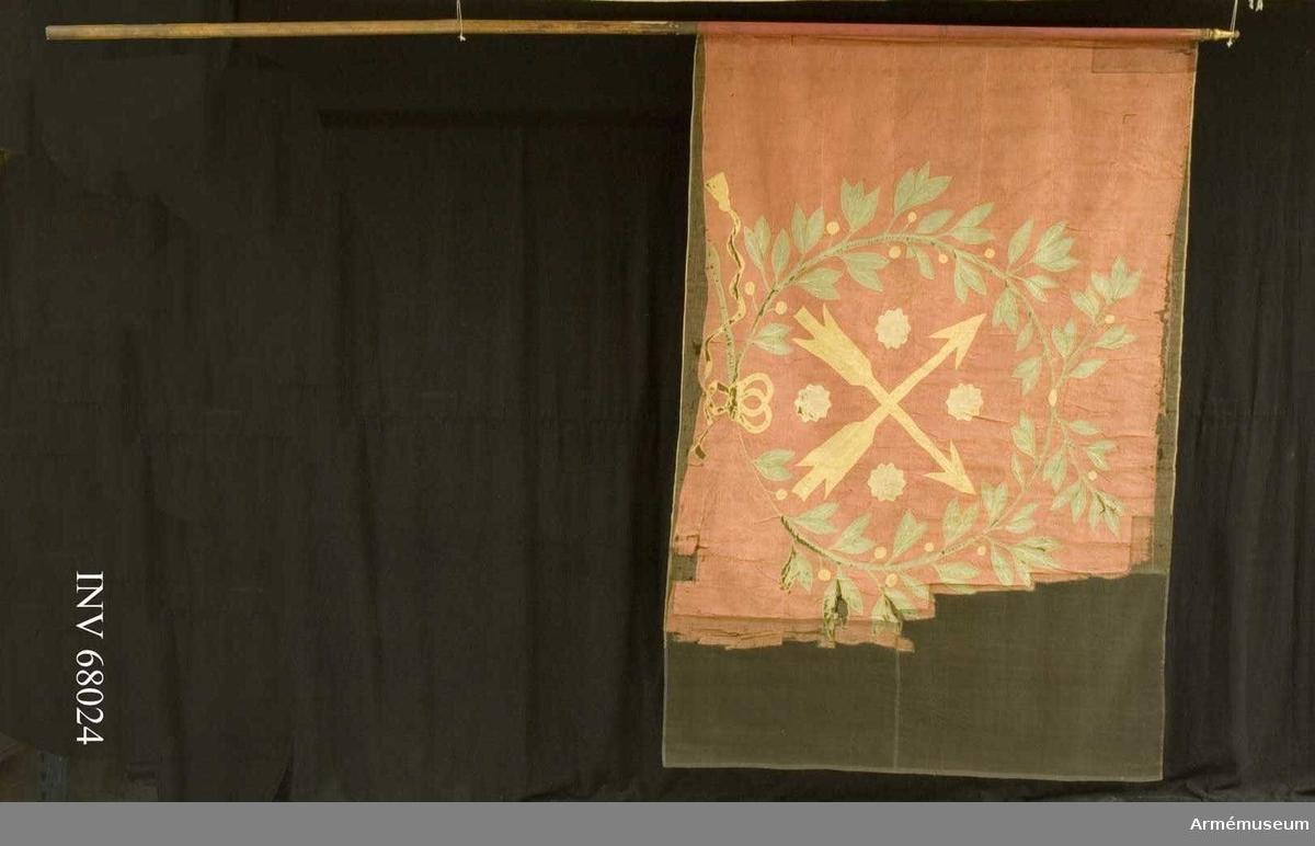 Duk: Tillverkad av enkel röd sidentaft, sydd av två horisontella våder. Fäst vid stången med en rad tennlickor på ett gult sidenband.  Dekor: Närkes sköldemärke i intarsia: två korsade pilar i gul sidentaft följda av fyra i vinklarna ställda rosor i vitt. Allt omgivet med en stor krans av två lagerkvistar i grön sidentaft med blad och gula bär, upptill och nedtill hopknuten, nedtill i gul rosett med fladdrande tofsprydda ändar. Kransens konturer broderade med silke (plattsöm).  Stång: Tillverkad av brunmålad furu, avsågad. Förlängning av mässing.
