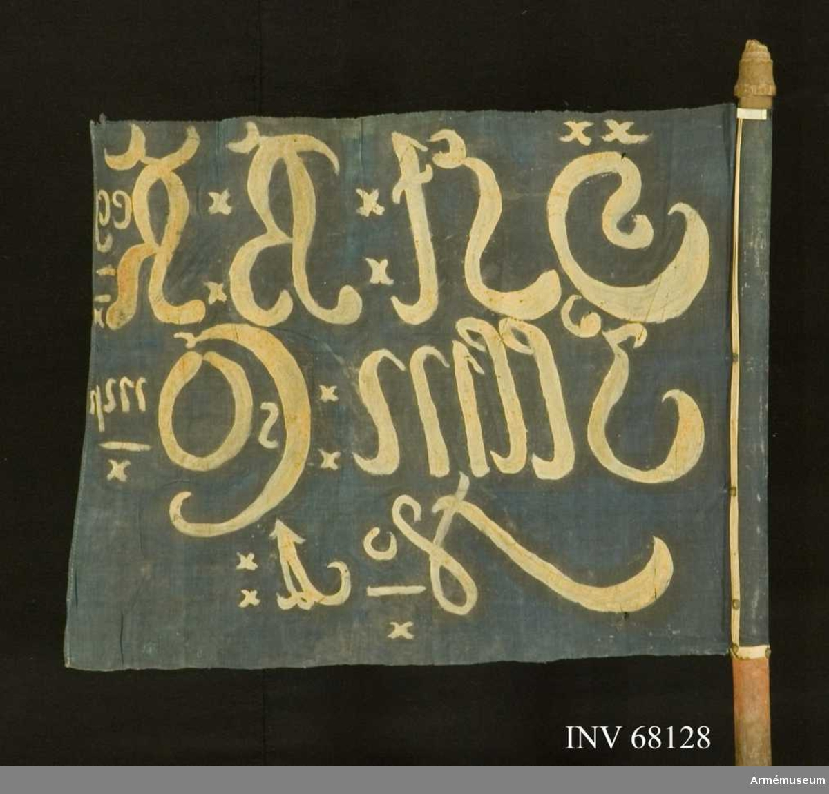 Duk: Tillverkad av enkel blåmålad linnelärft. Fäst vid stången med 1 rad tennlickor på ett vitt band.  Dekor: Målad omvänt lika på båda sidor i vitt på tre rader.  Stång: Tillverkad av rödmålad(?) furu. Nedtillen doppsko av järn i form av en pik.