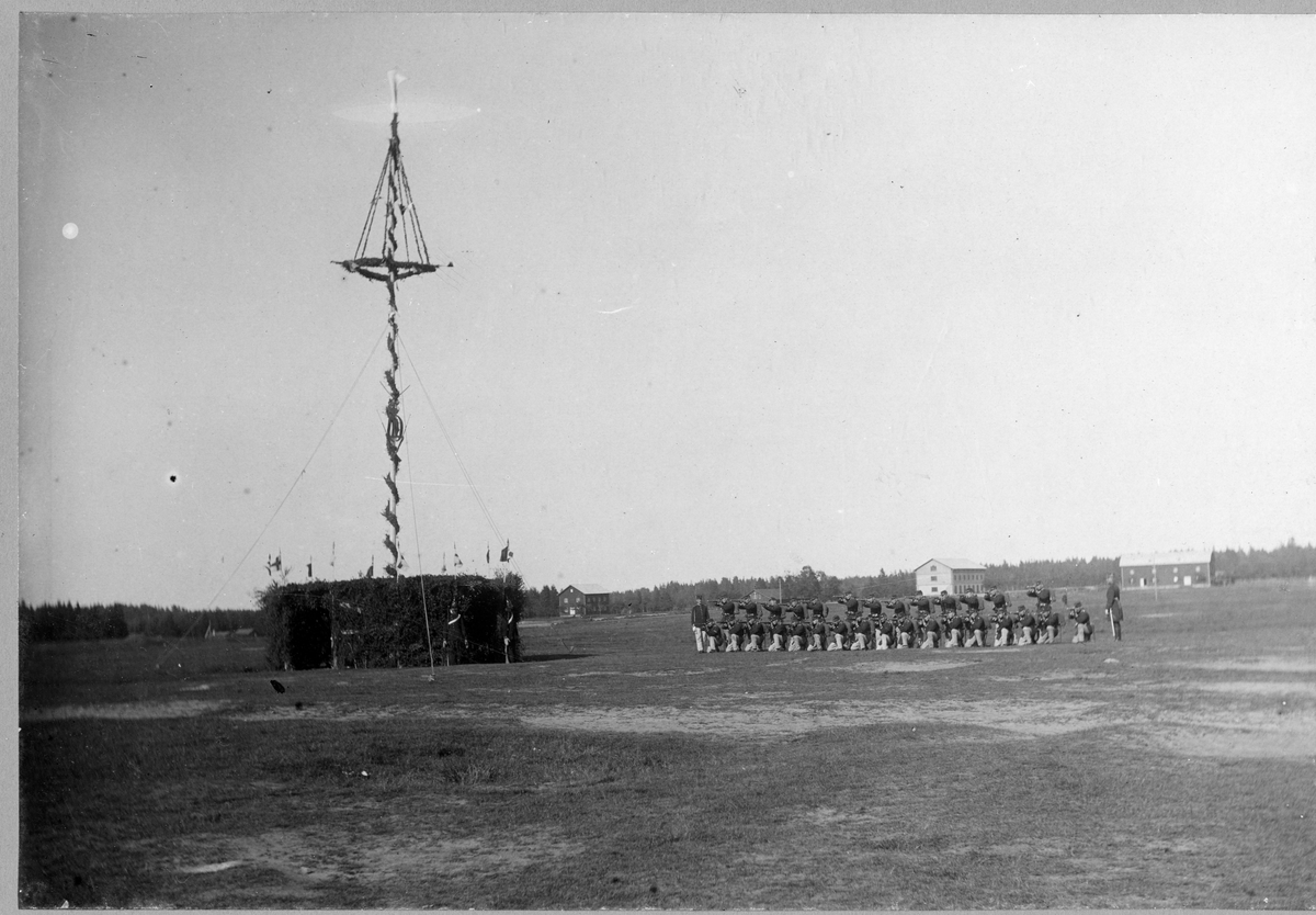 Soldater ur Älvsborgs regemente I 15 i skyttelinje framför omkringbyggd majstång på Fristad hed.
