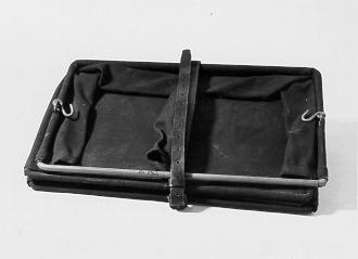 Bälgfack, fack med järnställning klädd med svart tyg. Upptillpå sidorna finns krokar för fackets upphängning. Sex lika storafackavdelningar. Försett med läderrem för fackets sammanhållande, dådet inte används.