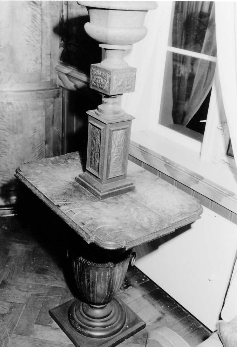 Kvadratisk fotplate, urneformet sokkel; plate buet og knekket i hj.; oppsats m. 2 utvidelser m. kvadratisk tverrsnitt, på sidene drevne metallplater, øverst urne m. sinkbeholder.