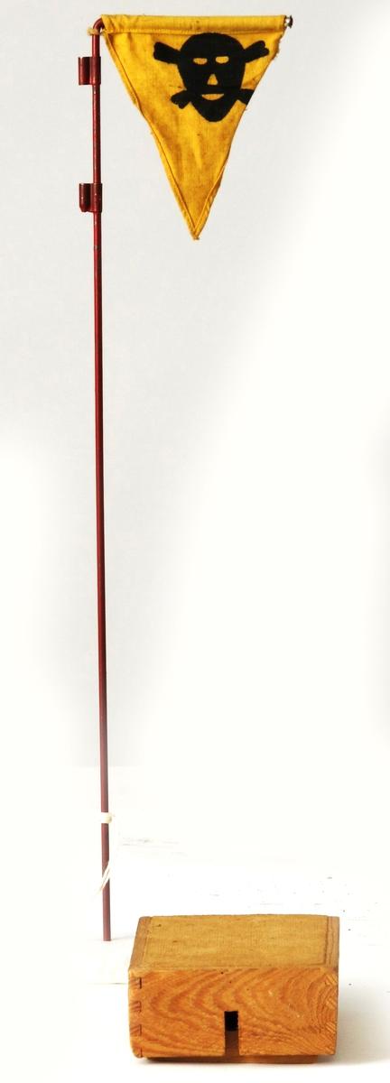 Furu  og   fiberplate  rektangulær eske med fiberplate bunn,  forsynt med ca 1. 5 DI. rundt hull  i ene kortside. Til denne eske hengslet  i bak kant lokk med tre sider og  fiberplate topp. Lokket forsynt med  med 0.6cm bred spalte som med lokket  i lukket tilstand kommer rett foran  eskens hull. Her sanns. anbragt  tenmekaniske som antenner eskens  sprengstoff når lokket presses helt  ned i lukket stilling ved trykk av  fot eller tilsvarende vekt.  Tilst. januar 1964: ubrukt, god,  karakteristisk for norsk  krigsproduksjons standard.
