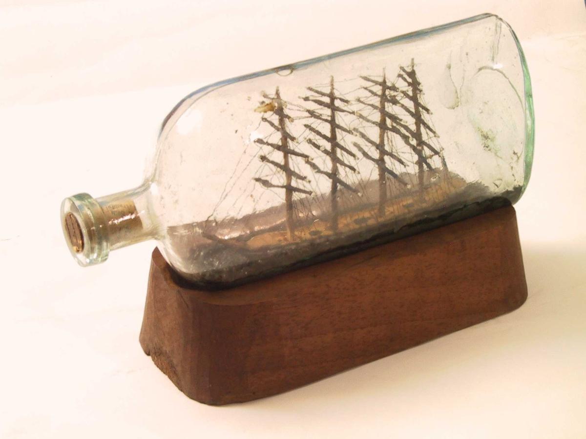 """Skute i flaske.  Frivaktsarbeid.  a) Flaske klart, lyst grønnlig   glass,  flattrykt """"lerkeform"""".   b). Flasken ligger på fotstykke (løst) av   valnøtt,  Inne i flasken et firemastet seilskip m. kanonporter. Ligger meget  dypt i """"vannet"""", som består av en blank, ujevn, grågrønn masse.  Skipet har flagg m. 3 liggende striper, nederste rød, midtre blå, øvre hvit.  Nokså ubehjelpelig og klosset urført frivaktsarb.  Tilst 1966. god."""