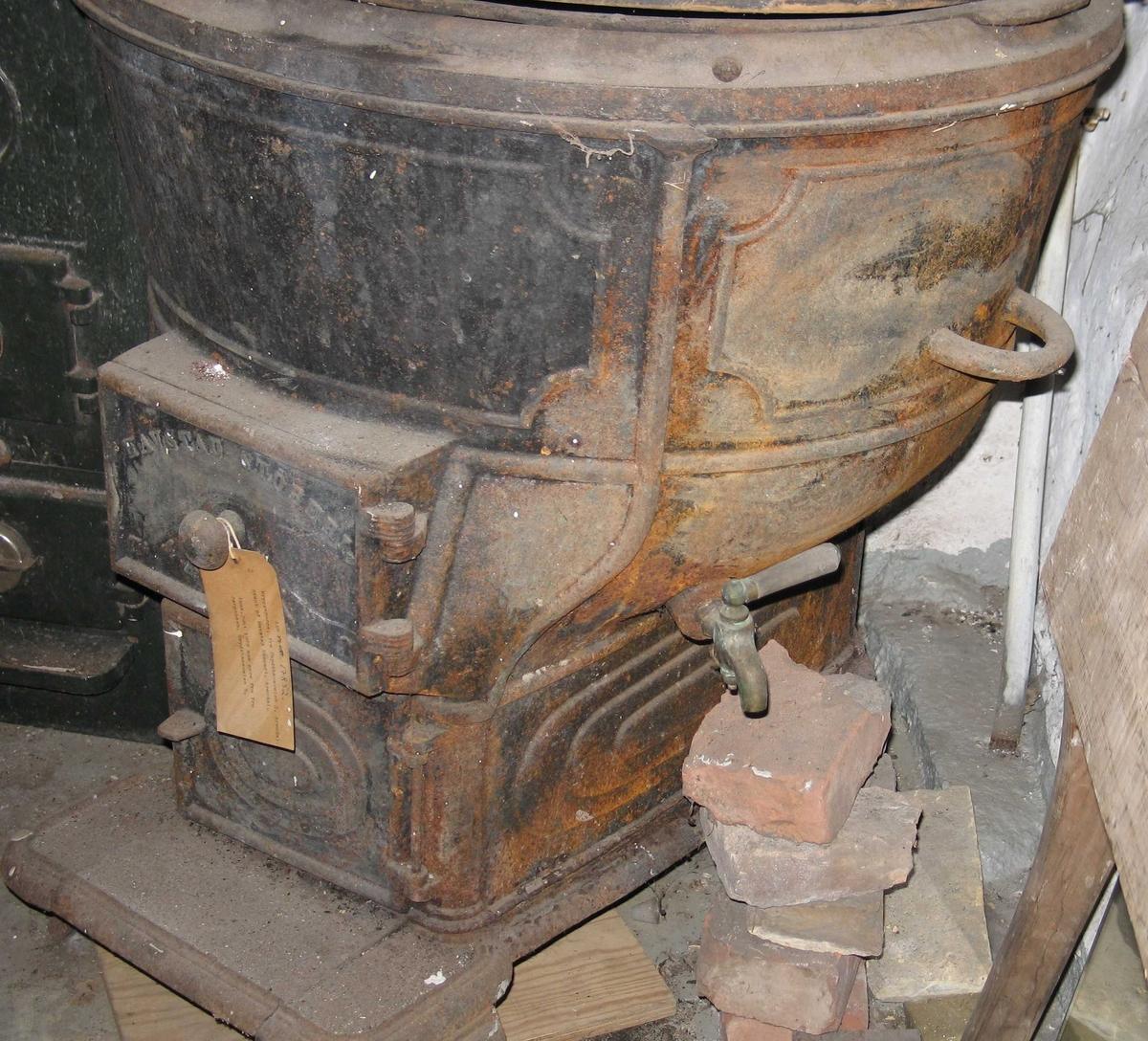 Bryggepanne, komplett. Støpejern, trelokk med tre labanker oppå, og midthank.  Stor bryggepanne med oppoverskrånende doble vegger.  Står på ovn med en dør for ilegg.  Støperiets navn er stemplet på døren.  Under den en dør for askeuttak.  En hank på hver side av gryten.  Kran for uttapping.  Panna sto i kjelleren da giver kjøpte huset i 1979.  Med tilhørende rør = komplett.  Står i kjelleren på husmorskolen.