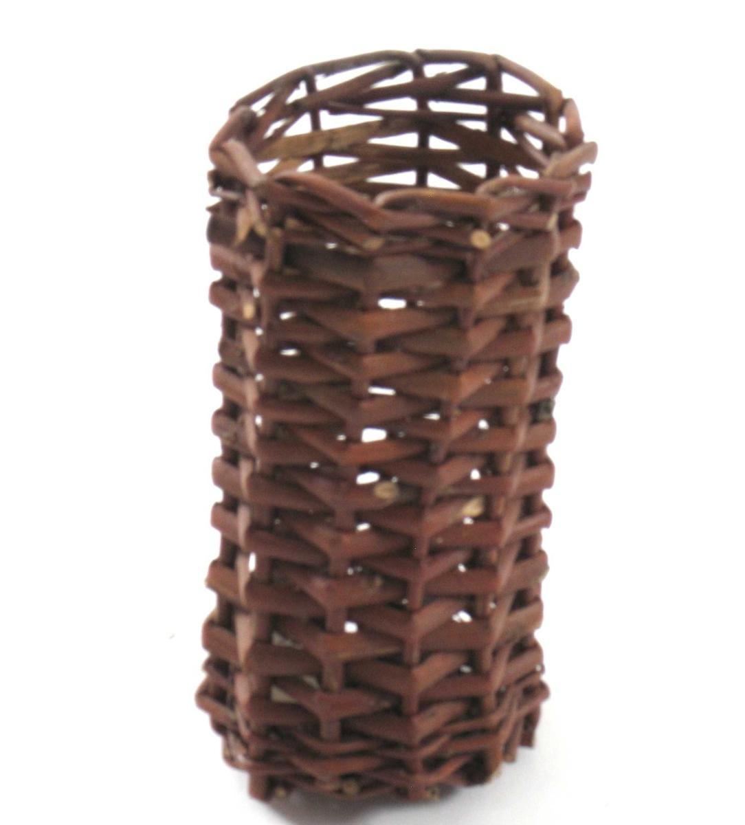 Rund, sylindrisk flettet kurv. Flettet av ubarkede pilekvister. En liten blikkplate er bundet fast til kurven. Fire av de fem kurvene er samlet i en større og enklere firkantet bærekurv av trelister med en bøyd hank over.