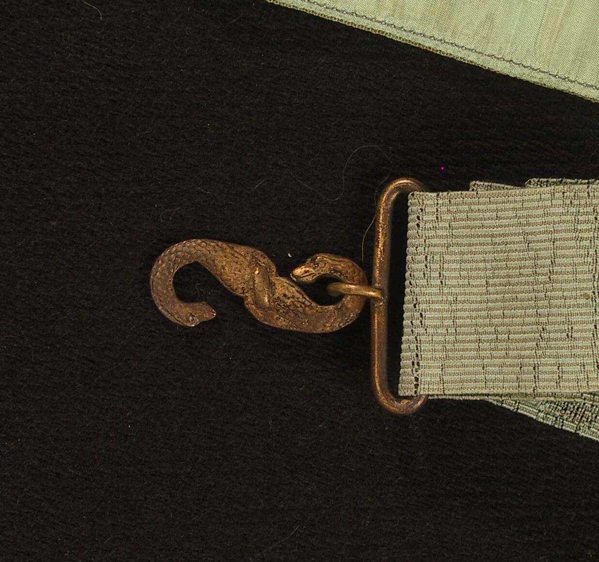 Rosetter, hengende bånd avsluttet med en spiral i metalltråd på tvers og syv spiraler hengende fra denne.