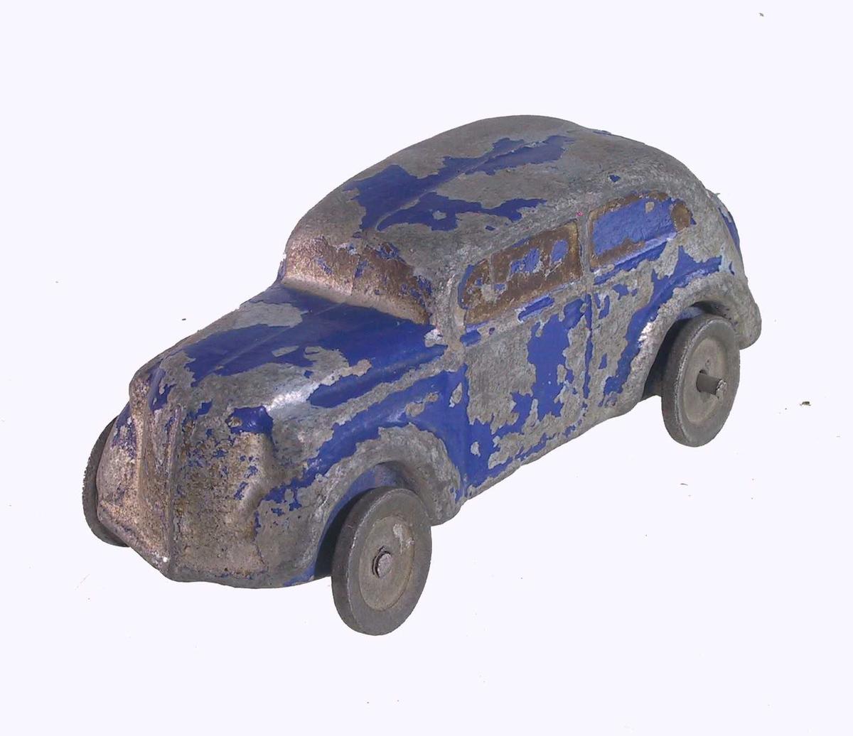 Form: Lekebil formet som personbil, støpt i et stykke, med løse hjul festet på stift foran og bak.