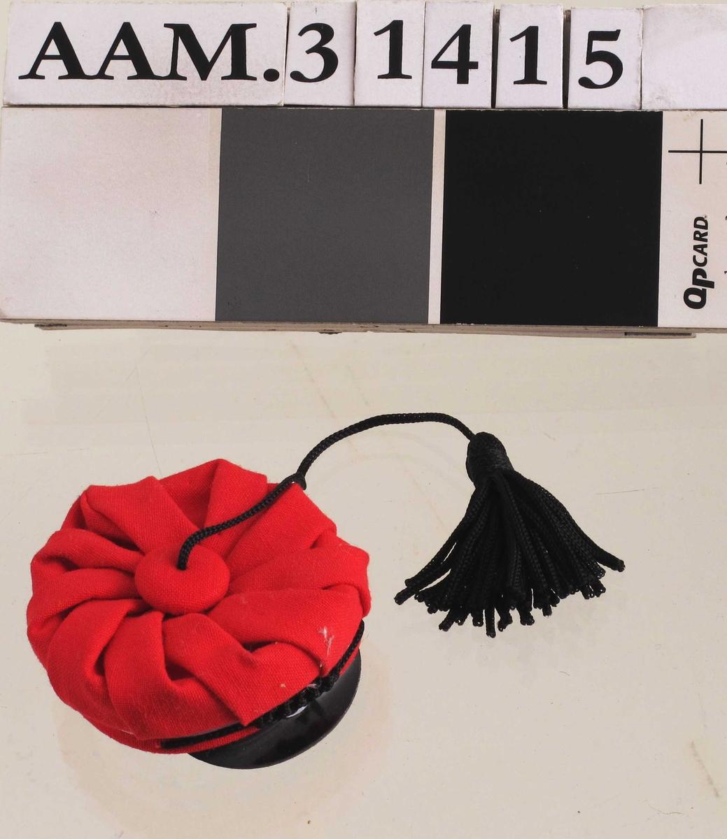 """Rød russelue, svart brem, svart dusk i lang tråd .  Over bremmen et emblem av """"silke"""" med sirkler i fargene hvit, blå og rød.  Over emblemet en sort snor med fletting på midten.    Miniatyr"""