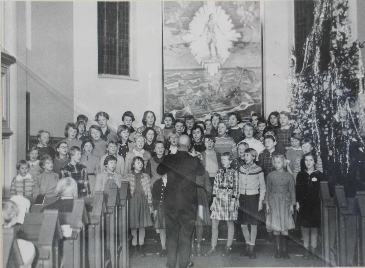 Elever fra 5, 6 og 7 klasse ved  Barbu skole synger i Barbu kirke på julaften 1956. Alterbilde i bakgrunnen, stort juletre til høyre.