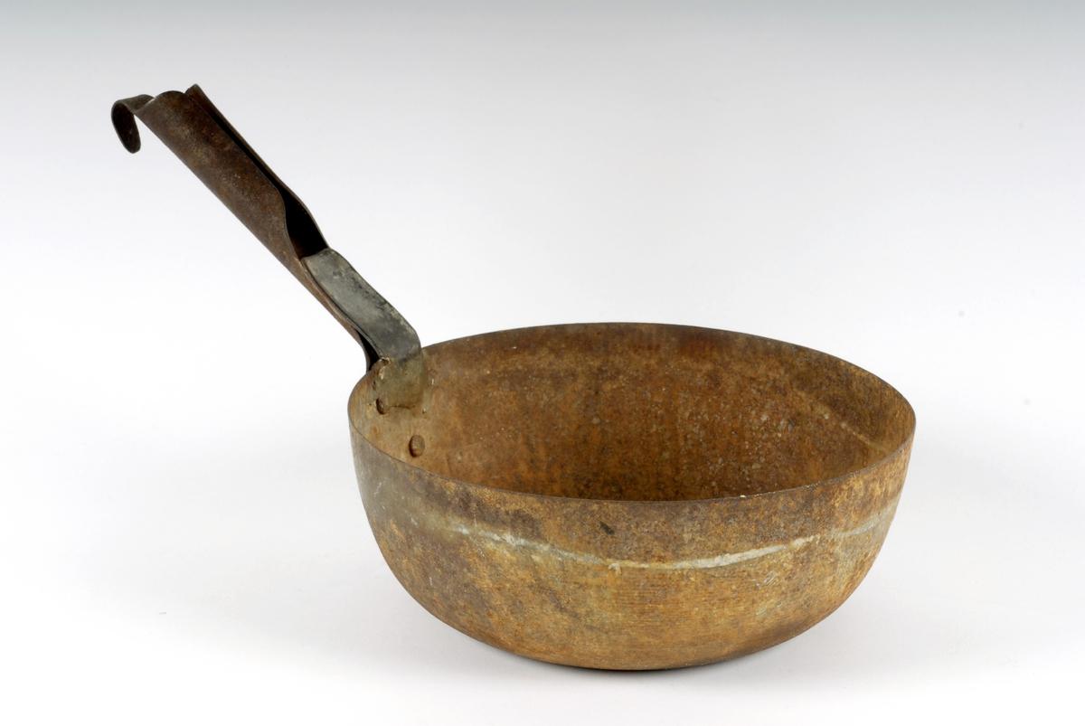 """Form: Rund, m/flat hvelvet botn Hanken er brettet rund, med krok i enden for oppheng. Klinket til koppen med tre nagler. Den har vært brukket innved hanke- festet og er reparert ved at den er sveiset på igjen med et stykke sink på oversida. Tidl. reg.: """"Ause (skaupe) til vatn - Fløtten"""".  Iflg. J.E. Horgen er skaupe det vanlige (brukte) ordet i området."""