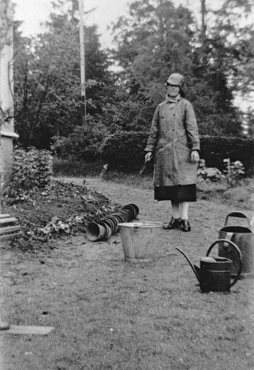 Fru dr. Eger(Callik) arbeider med planter i haven, våren 1927. Planteskje i hånden og tomme potter foran bedet, sinkbøtte og vannkanner oppstilt til bruk.
