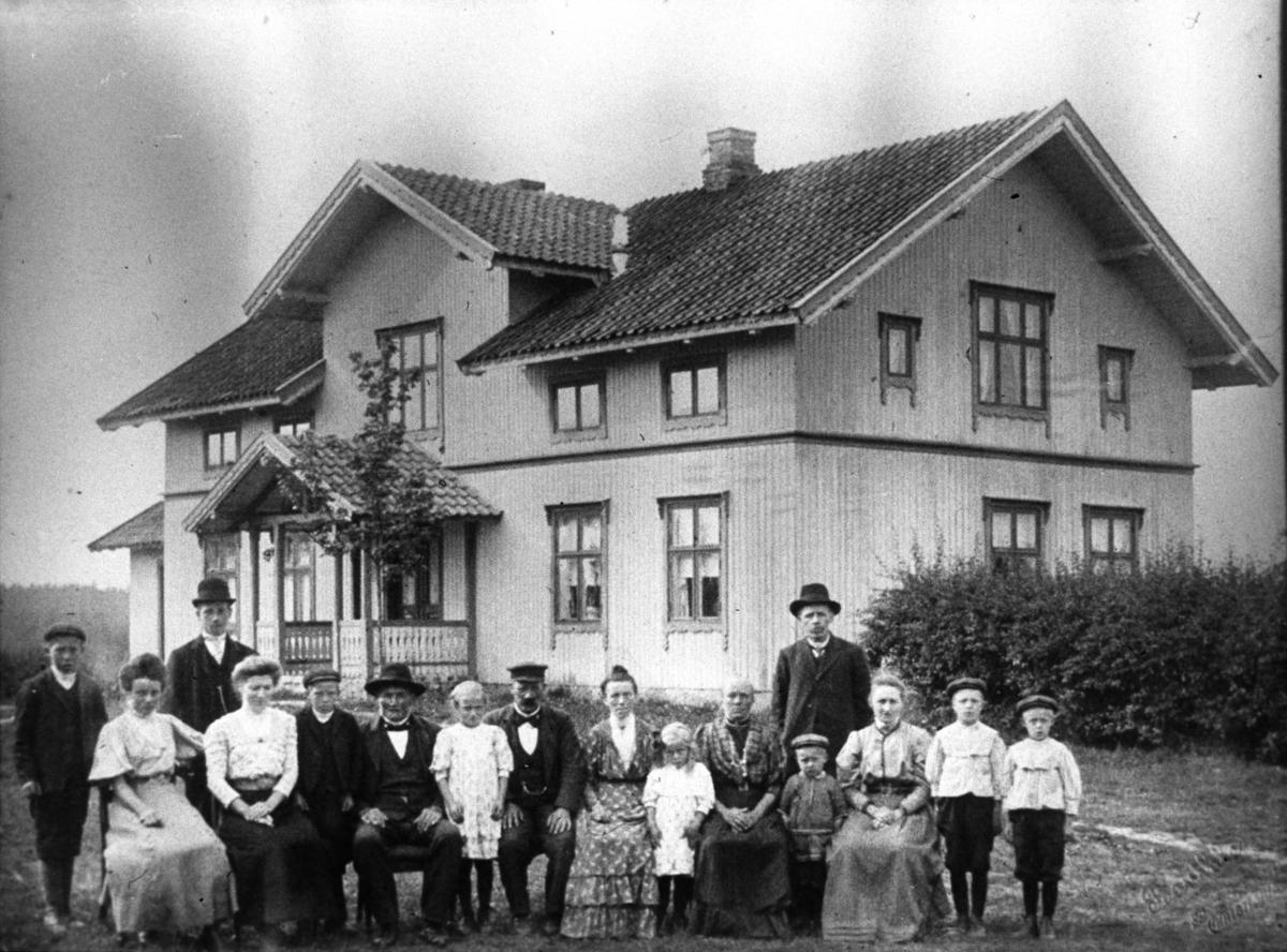 Gruppe med menn, kvinner og barn foran et bolighus.