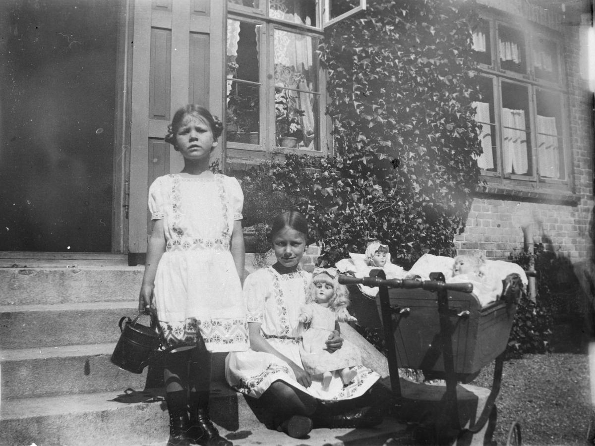 To jenter på trappen foran et hus, med dukker og dukkevogn.