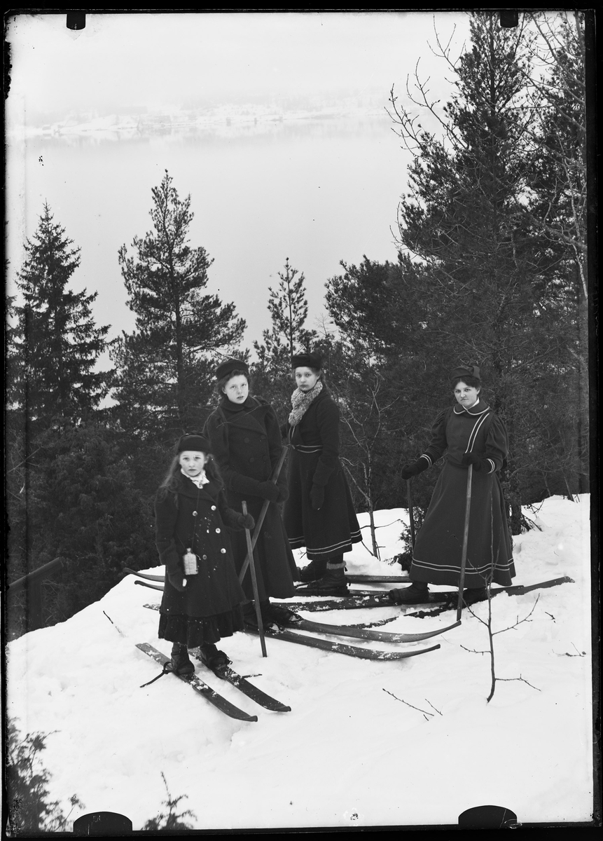 Kvinner i skidrakter på ski i skogen.