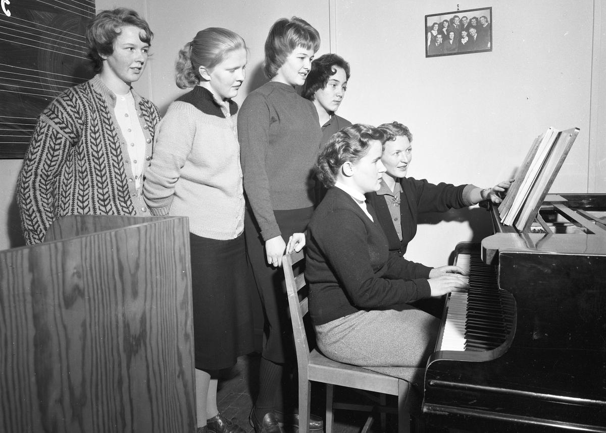 Romerike Folkehøyskole. Jenter ved et piano.
