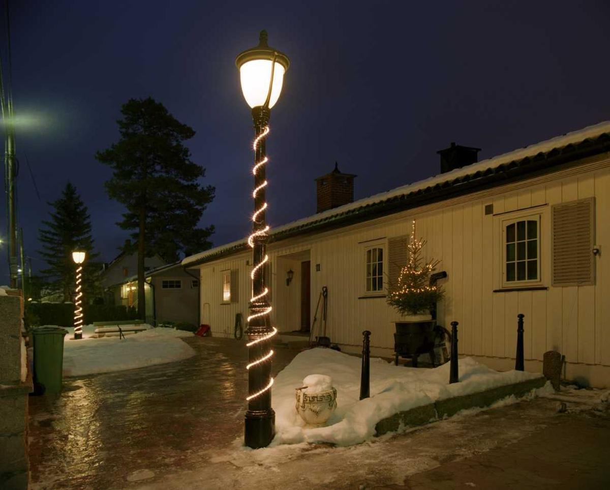 Julebelysning  Hvit lysslange rundt lykte og hvit lyslenke på liten gran ved husvegg ved tomannsbolig