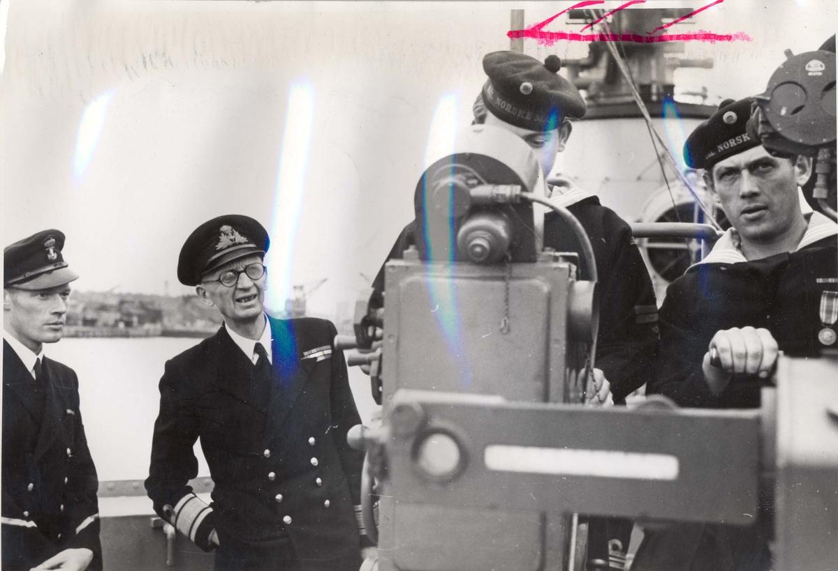 """Jageren """"Stord"""" blir overtatt av Den Norske Marine, 26.august 1943. Kontreadmiral E. Corneliussen inspiserer en Bofors-kanon, som bemannes av 13 mann"""