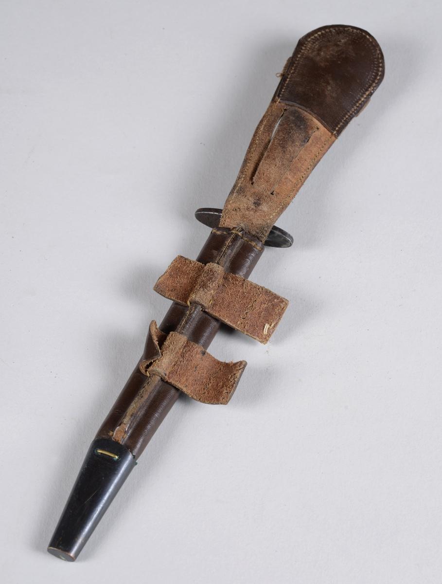 Dolk av jern i lærhylster.  Hylsteret er forsterket i spissen og kan festes i belte. Dolken har et ruglete håndtak og et toegget blad med midtribbe.